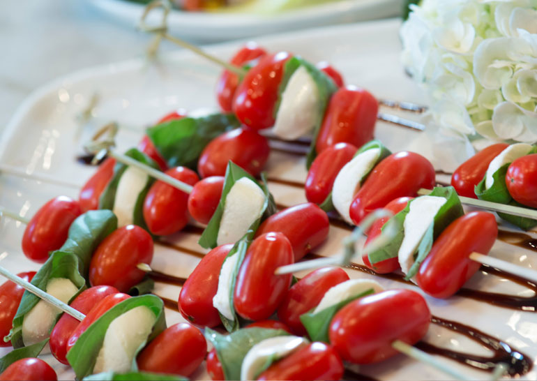 Mozzarella, tomato and basil skewers with a balsamic drizzle ready to be served at a Maison in home party